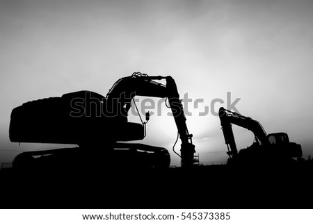 Silhouette of excavator at construction site in oilfield - sunset blue hour- black and white