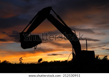 silhouette of excavator loader at construction site - stock photo