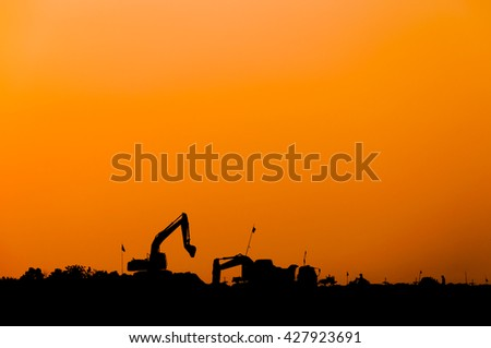 silhouette of excavator loader at construction site,Silhouette Backhoe,track-type loader excavator machine doing earthmoving - stock photo