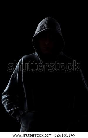 Silhouette of faceless guy in hoodie in the darkness, concepts of danger, crime, terror - stock photo