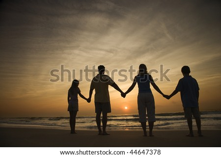 Silhouette of family holding hands on beach watching the sunset. Horizontally framed shot. - stock photo