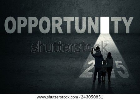 Silhouette of family in front of an opportunity door with number 2015 toward the future - stock photo