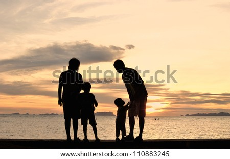 silhouette of family on the beach at dusk. - stock photo