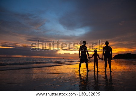 Silhouette of family on the beach at sunset - stock photo