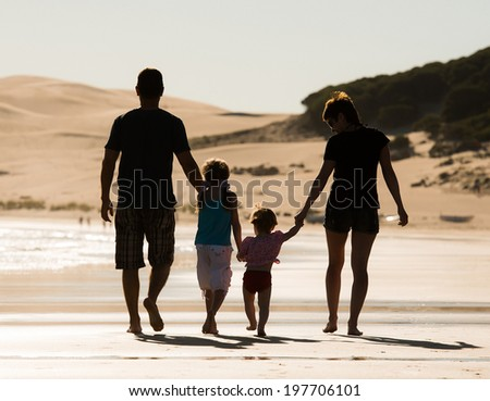 Silhouette of family, two adults and a child at the coast in sunset - stock photo