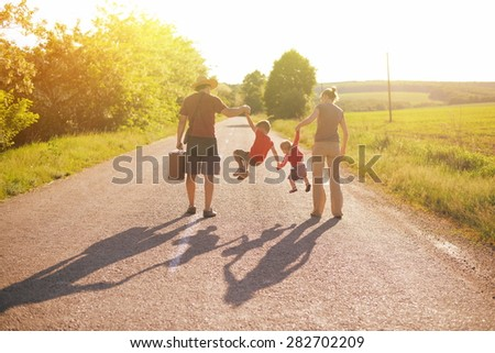 silhouette of family walking in park on sunrise - stock photo