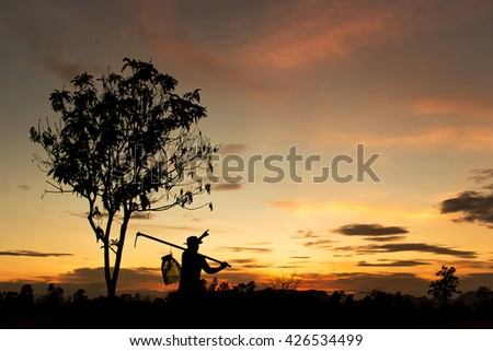 Silhouette of farmer pointing at sky for dreaming. harvesting and agriculture conceptual background. dark twilight time.