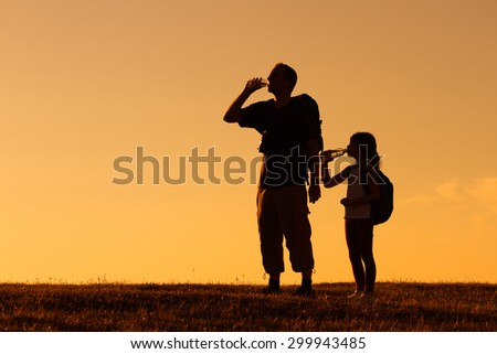 Silhouette of father and daughter resting of hiking and drinking water.Refreshment for father and daughter hikers - stock photo