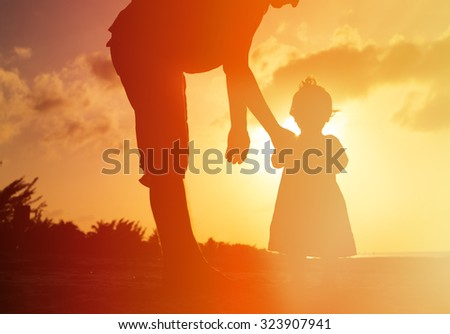 Silhouette of father and little daughter on sunset beach