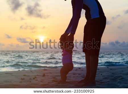 Silhouette of father and little daughter walking on sunset beach