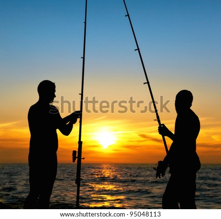 Silhouette of father and son fishing at sunset - stock photo