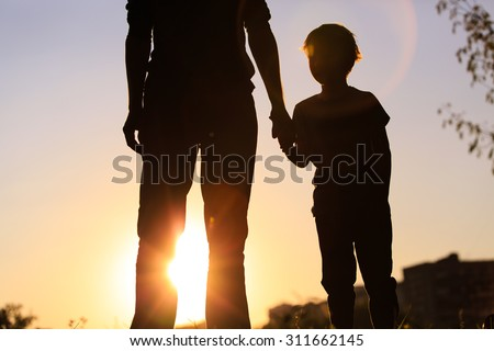 silhouette of father and son holding hands at sunset sky - stock photo