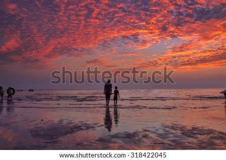 Silhouette of father and son holding hands walking on the beach at sunset sky - stock photo