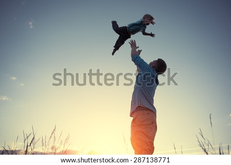 silhouette of father catching his son in the park at sunset (intentional sun glare and vintage color) - stock photo