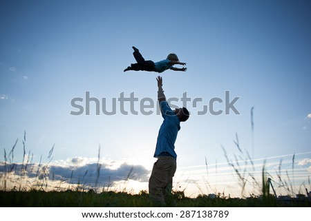 silhouette of father catching his son in the park in the evening - stock photo