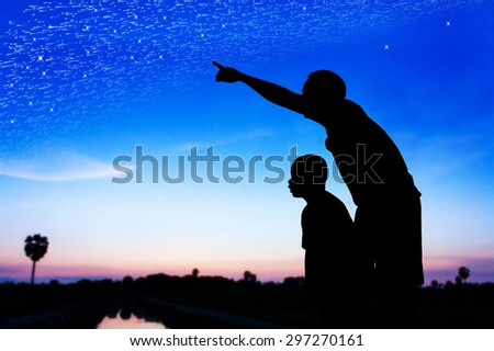 Silhouette of father use hand point his son look at meteor shower and star on the sky - stock photo