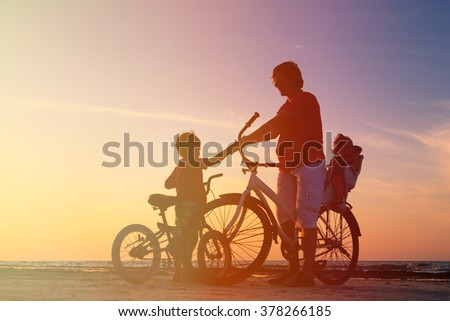 silhouette of father with two kids on bikes - stock photo