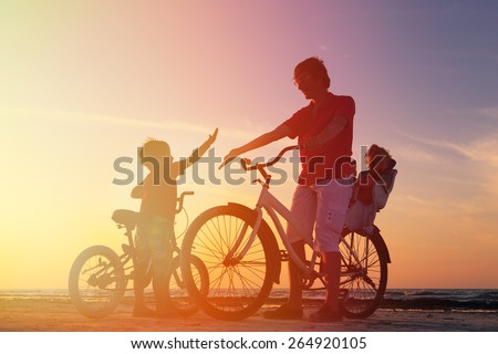 silhouette of father with two kids on bikes at sunset - stock photo