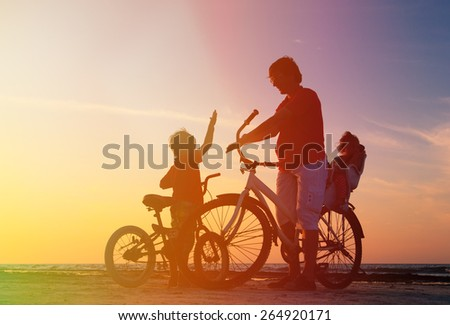 silhouette of father with two kids on bikes at sunset