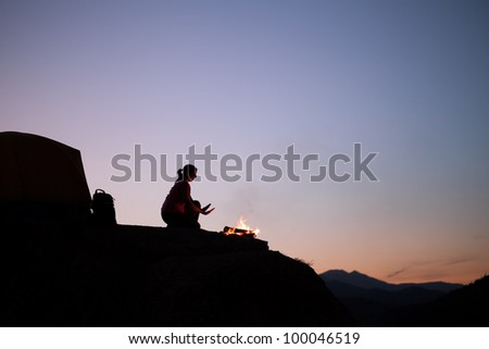 Silhouette of Female Camper Staying Warm by the Campfire - stock photo