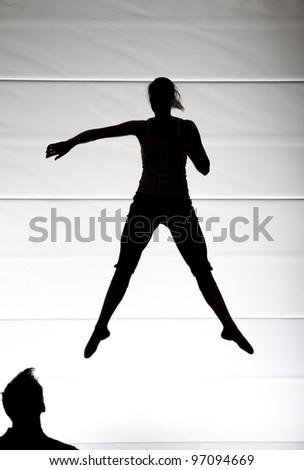 silhouette of female dancer jumping - stock photo