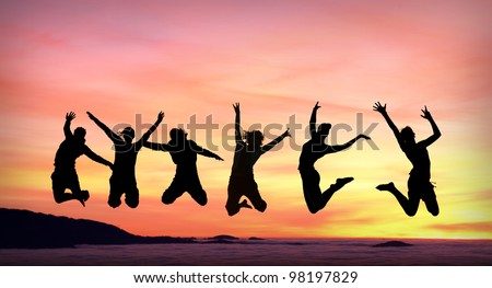 silhouette of female friends jumping in sunset - stock photo