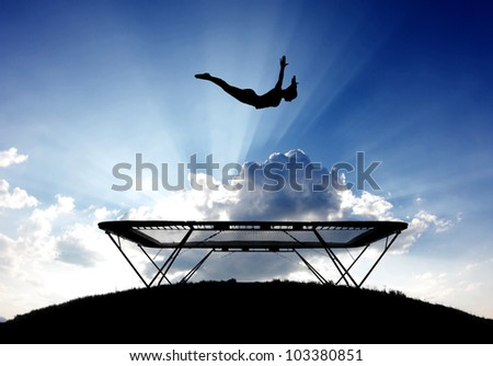 silhouette of female gymnast on trampoline in sky - stock photo