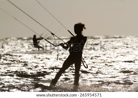 silhouette of female kite surfer in water - stock photo