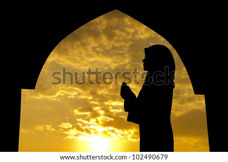 Silhouette of Female Muslim praying in mosque during sunset time - stock photo
