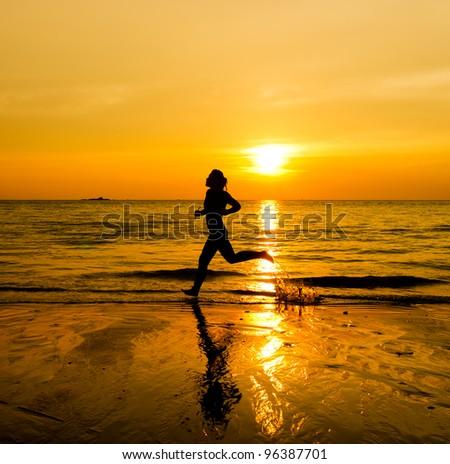 silhouette of female runner during sunset - stock photo