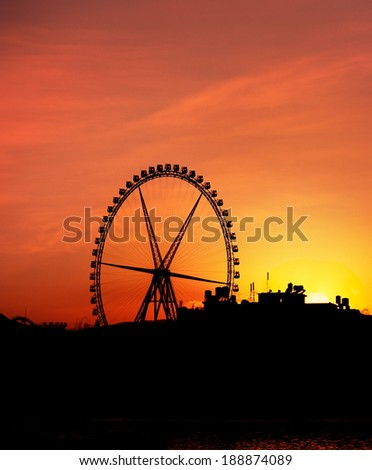 Silhouette of Ferris Wheel against the Orange and Yellow Sunset