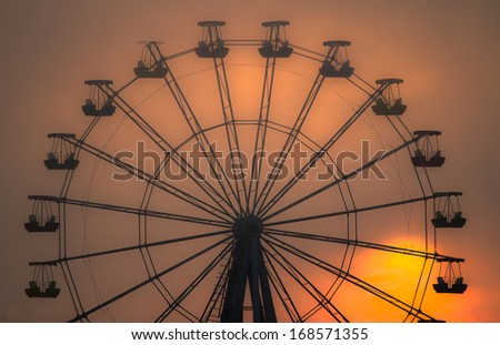 Silhouette of ferris wheel at sunset