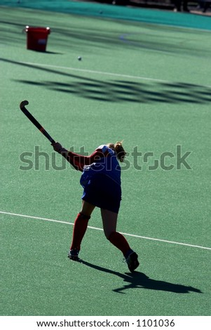 Silhouette of field hockey player during warm-ups.