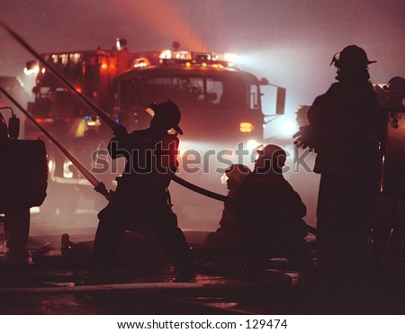 Silhouette of firemen and fire truck. - stock photo