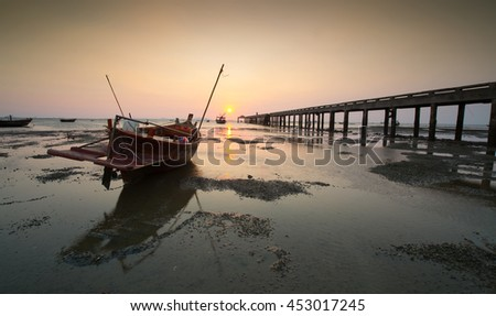 silhouette of  fisher boat  with yellow and orange  sunset - stock photo