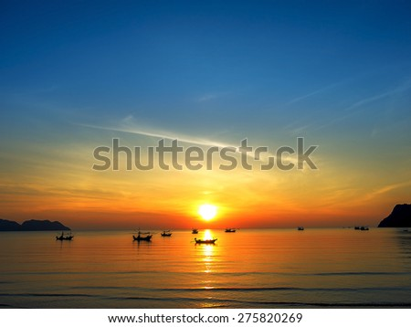 silhouette of fisher man's boats on the tropical sea with colorful sunrise on the sky - stock photo