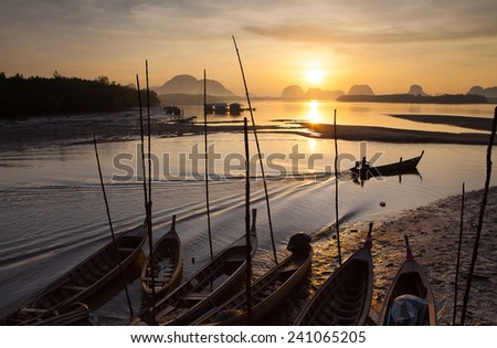 Silhouette of fisherman and traditional thai boats at Sam chong Tai, Phangnga province. - stock photo