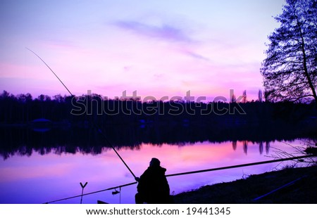 Silhouette of fisherman at sunset - stock photo