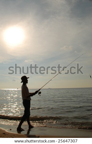 Silhouette of fisherman casting at sunset - stock photo