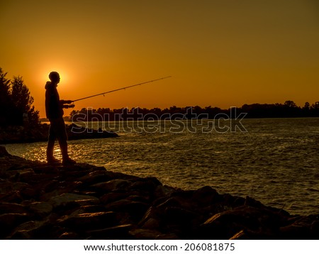 Silhouette of fisherman on river bank at sunset.