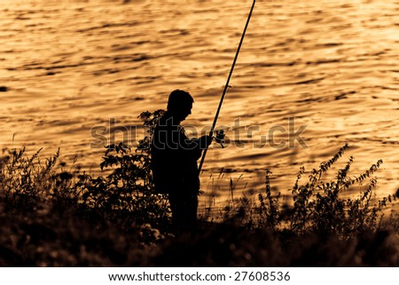 Silhouette of Fisherman on sunset. - stock photo