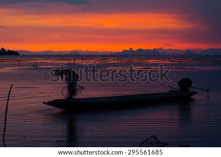 Silhouette of fisherman throwing fishing net during sunset