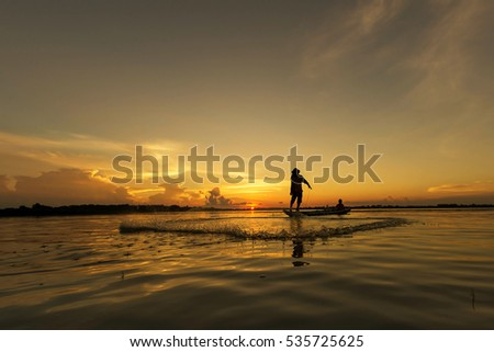 Silhouette of fisherman throwing net on the lake