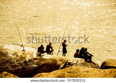 Silhouette of fishermen, Copacabana beach, Rio de Janairo, Brazil - stock photo