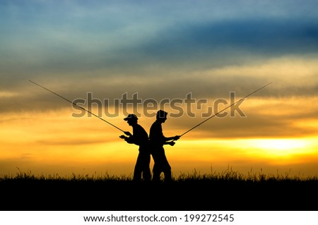 Silhouette of fishermen in sunset. - stock photo