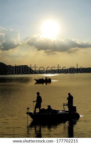 Silhouette of fishermen on dam water - stock photo