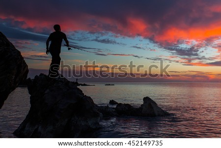 Silhouette of fishermen on the quiet sea with the rays of sunset