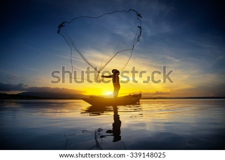 Silhouette of fishermen using nets to catch fish at the lake in the morning - stock photo