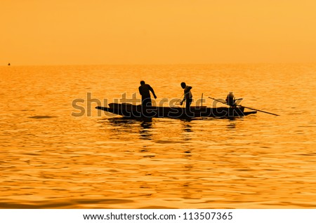 silhouette of fishermen with yellow and orange background - stock photo