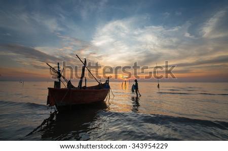 silhouette of fishermen with yellow and orange  sunset - stock photo